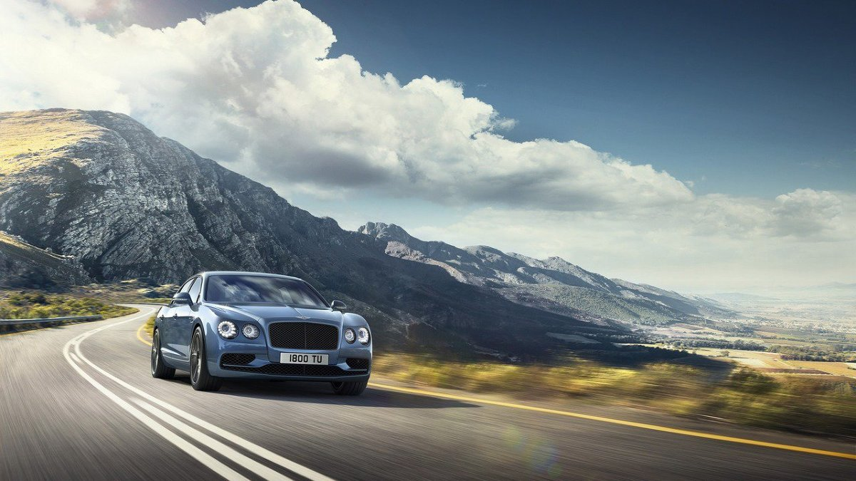 Bentley Flying Spur W12 S   Bentley Flying Spur W12 S został ozdobione czarnymi wstawkami. Przyciemniono tylne światła, natomiast charakteru pojazdowi dodają siedmioramienne felgi o średnicy 21-cali. We wnętrzu dominują ciemne barwy i pikowana skóra. Czerń kabiny zdecydowano się jednak przełamać jaśniejszymi, brązowymi wstawkami.  Fot. Bentley
