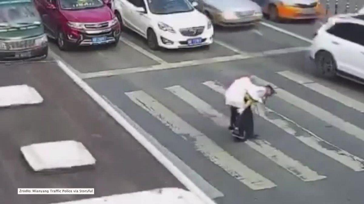 Chiński policjant na własnych plecach przeniósł przez pasy staruszka. Pomógł mu w ten sposób pokonać szeroką jezdnię w mieście Miangyang w środkowo zachodnich Chinach.  Fot. STORYFUL/x-news