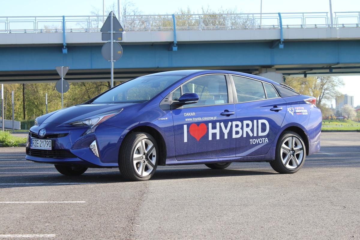"""Toyota Prius IV  Ceny Toyoty Prius zaczynają się od 119 900 za podstawową wersję wyposażenia """"Active"""". Standardem są w niej m.in. automatyczna klimatyzacja, adaptacyjny tempomat, 7 poduszek powietrznych, komputer pokładowy, kamera cofania. 127 900 zł kosztuje odmiana """"Premium"""", dodatkowo posiadająca m.in. podgrzewane przednie fotele i system umożliwiający otwieranie auta bez użycia kluczyka.   Fot. Bartosz Gubernat"""